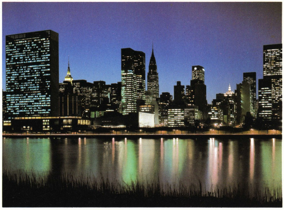 Night view of Midtown Manhattan looking southwest from the East River showing the One United Nations Plaza (center, left to Chrysler Building) completely illuminated. 1979.