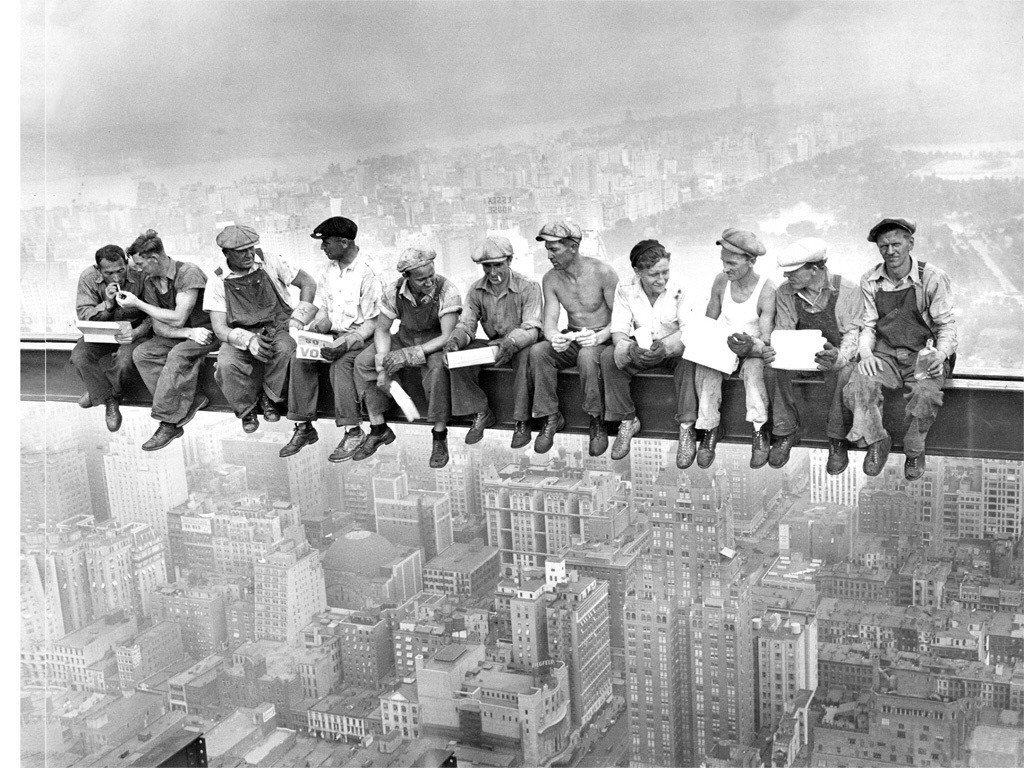 Fearless workers resting on a beam during the construction of the Empire State Building (1930).