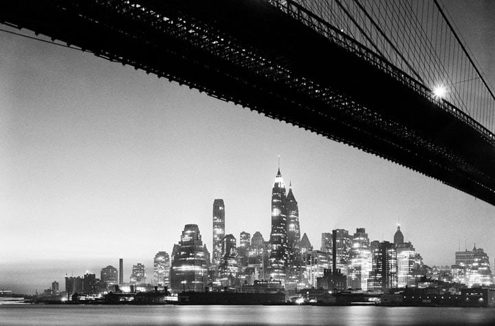 Lower Manhattan skyline at night, taken from underneath the Brooklyn Bridge in 1938.