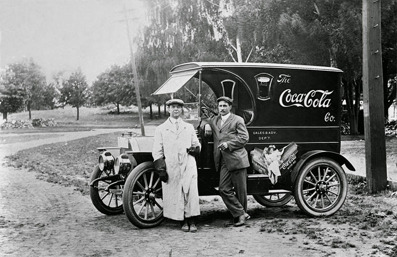 Two man stand in front of a Coca-Cola delivery truck, 1910.