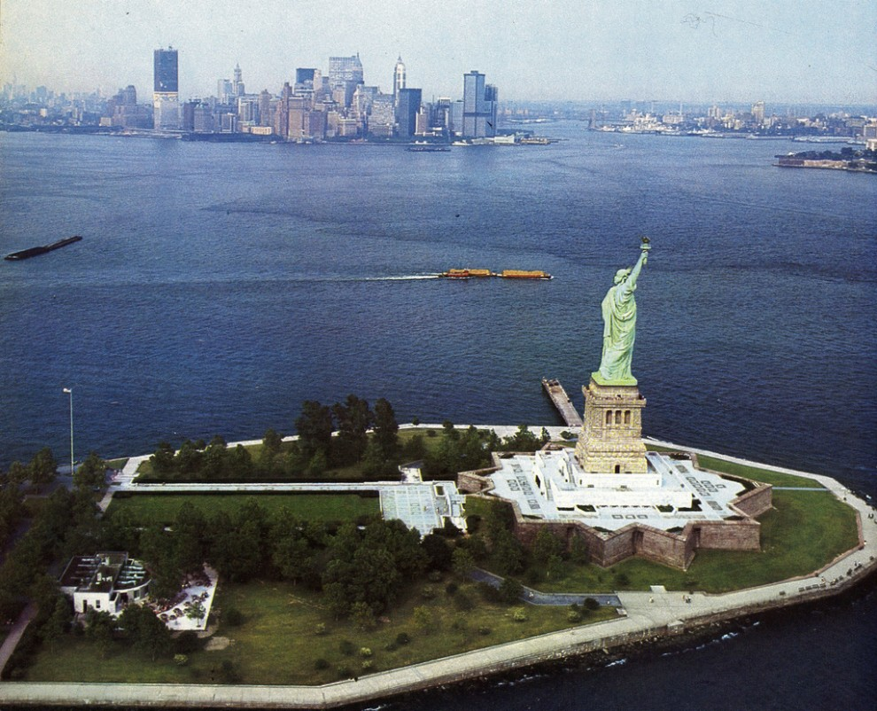 Aerial view of the Statue of Liberty with the new Twin Towers of the World Trade Center beginning to dominate the skyline. May 1970.